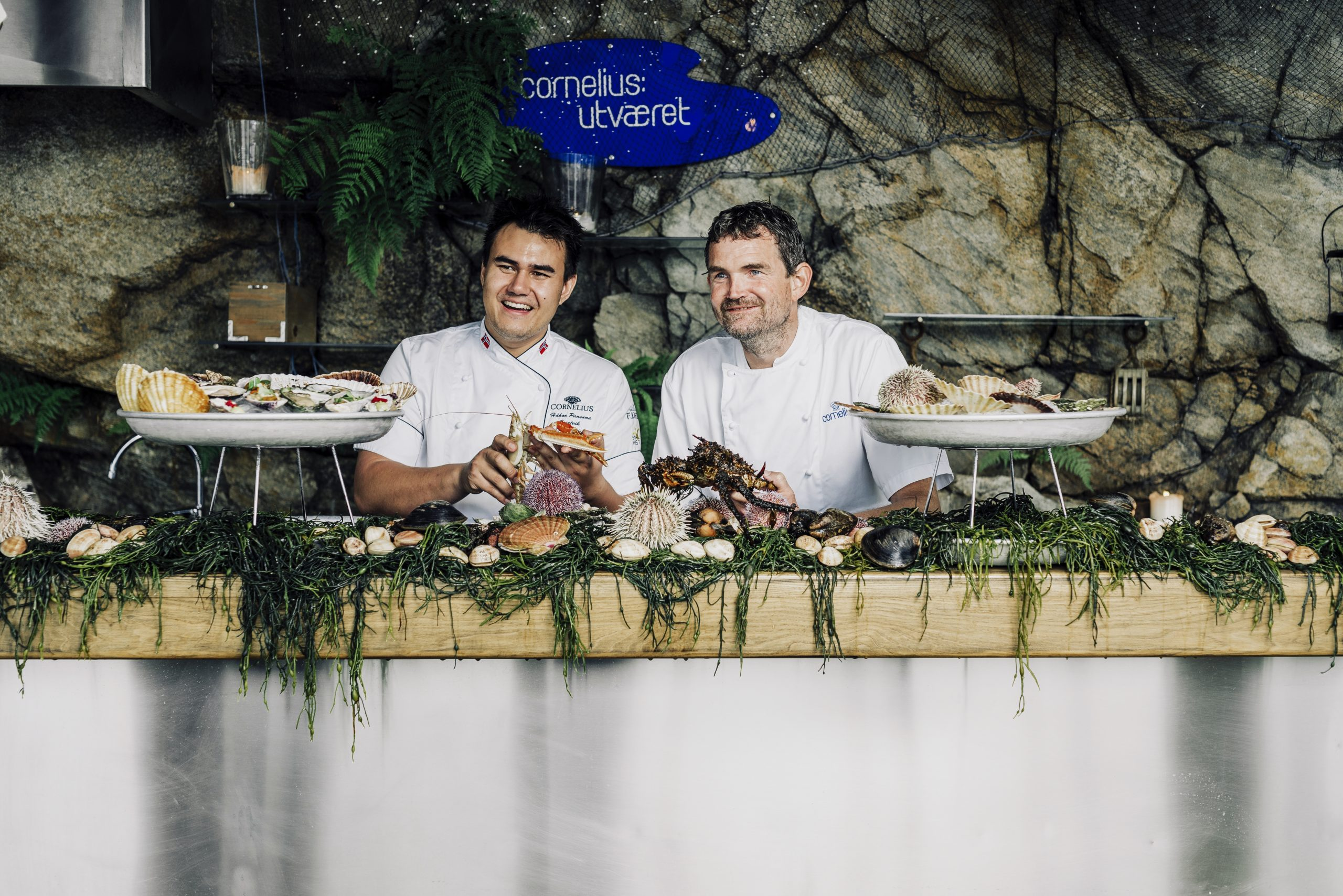 Two chefs sitting with seafood