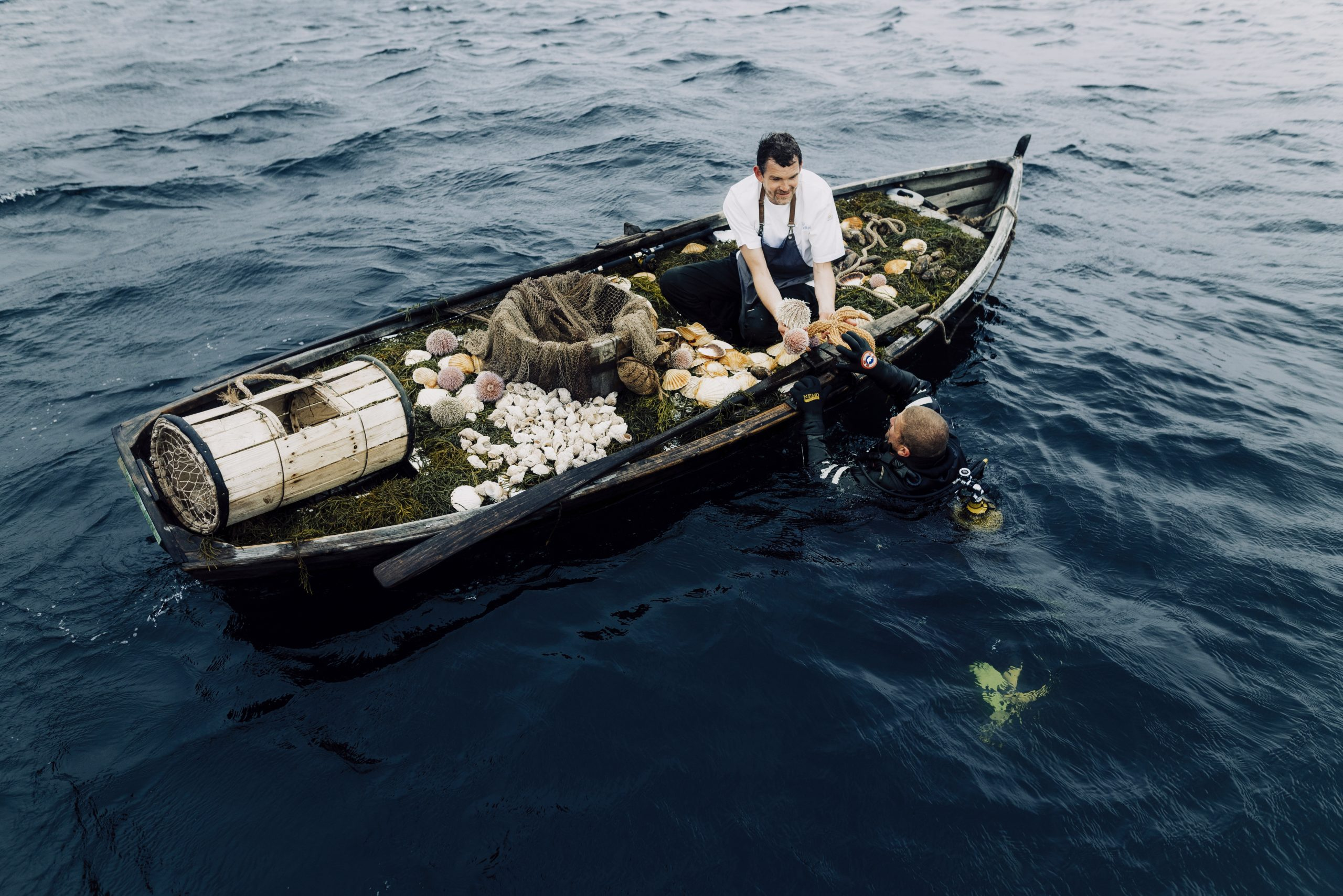 Cooking in rowboat receives seafood diver