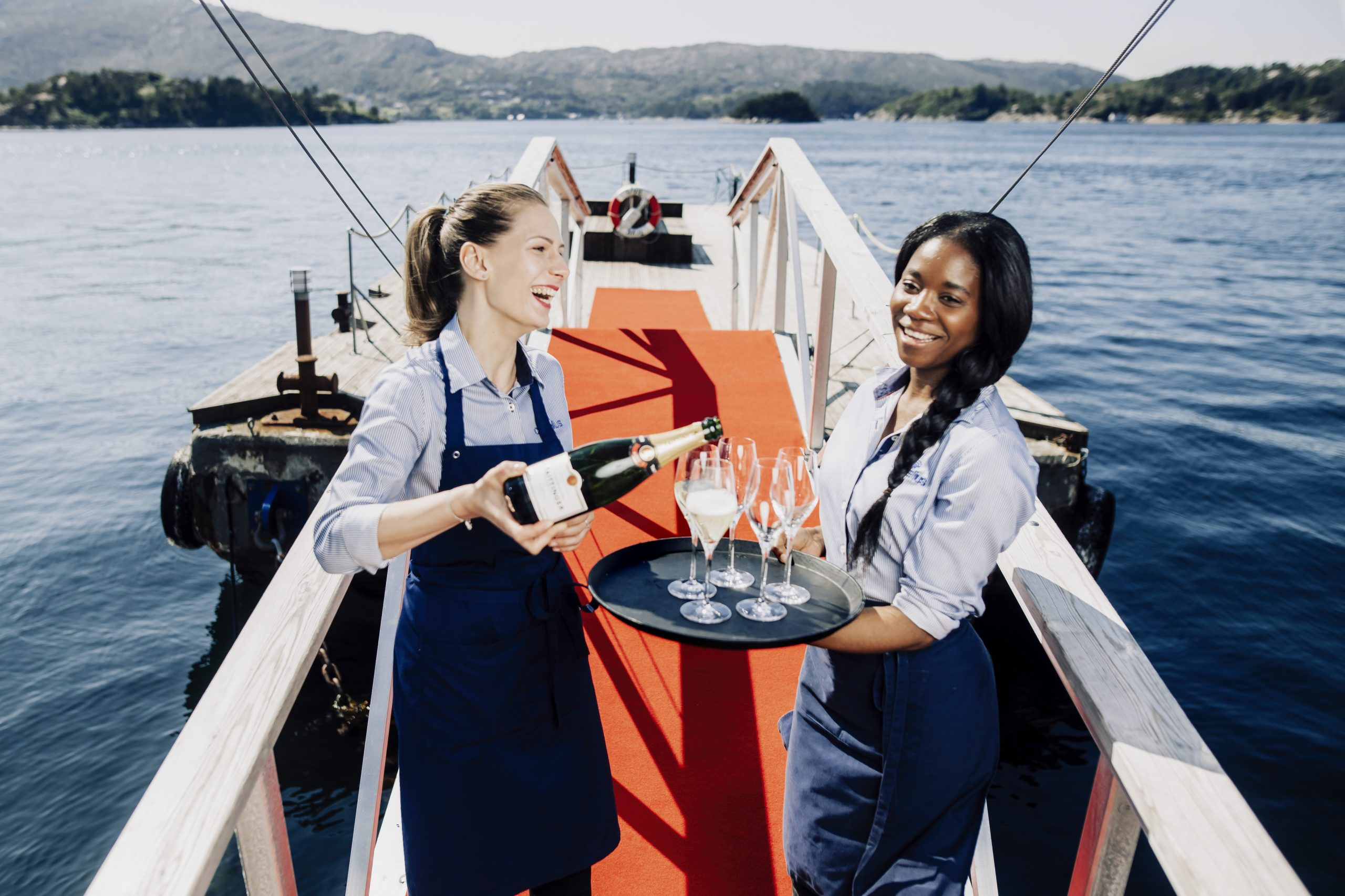 Two waiters rather sparkling wine in the glass on a pier