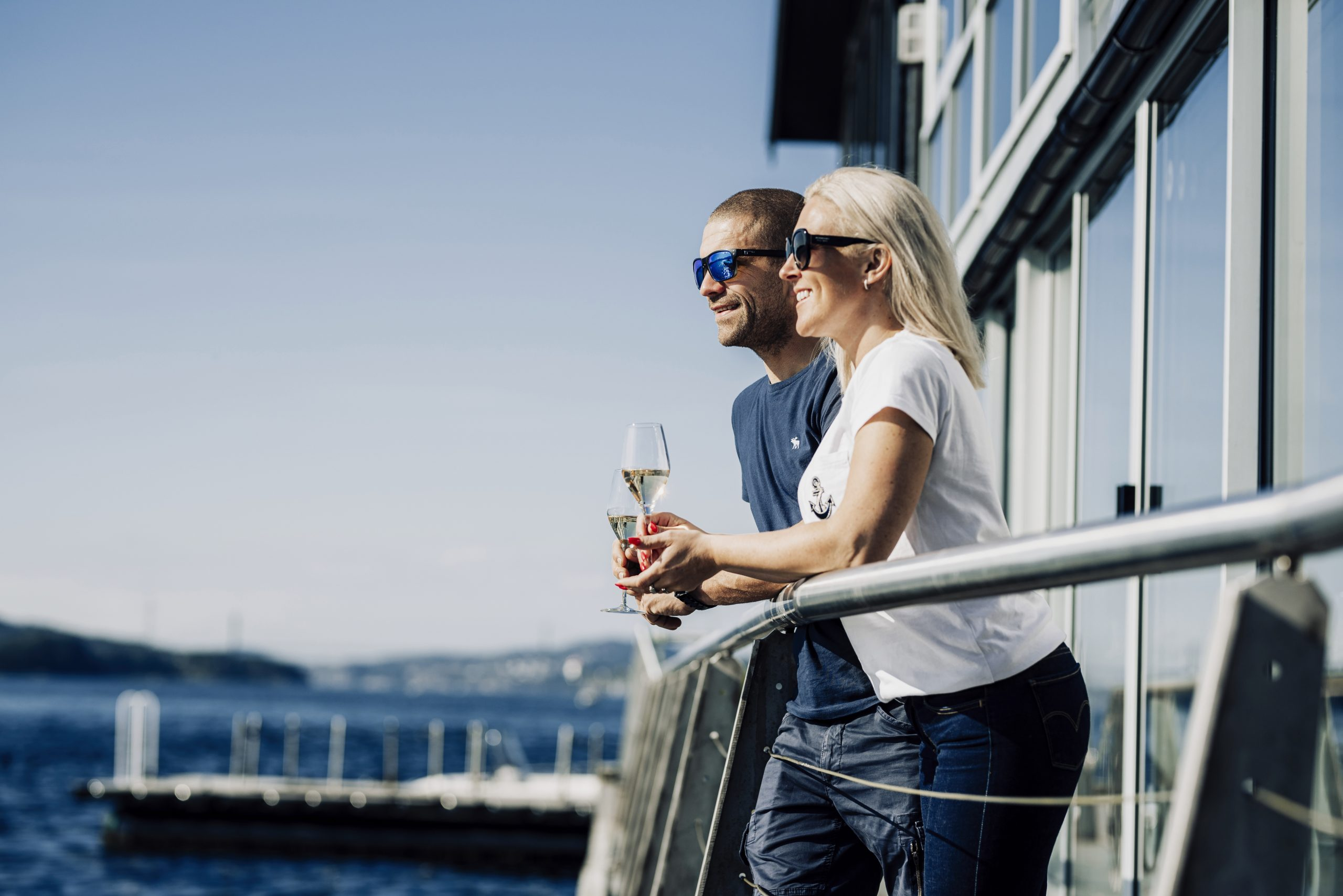 Two people with wine glasses standing along the quay